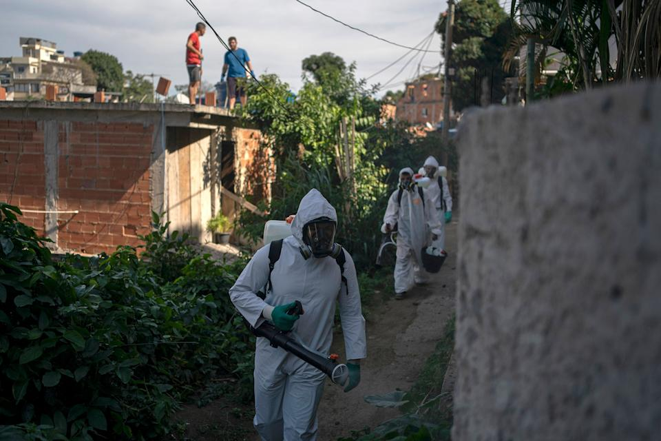 Volunteers spray disinfectant in an alleyway to help contain the spread of the new coronavirus in the Babilonia slum of Rio de Janeiro, Brazil, Sunday, July 12, 2020. (AP Photo/Leo Correa) (Photo: ASSOCIATED PRESS)