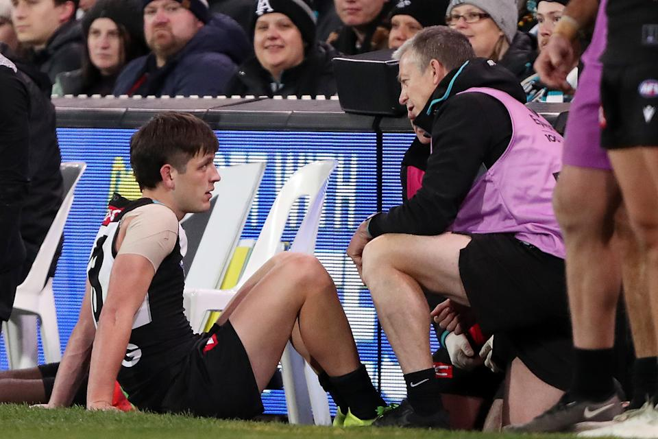 Seen here, Zak Butters is attending to by a Port medical staffer after suffering a knee injury.