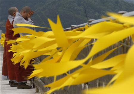 Buddhist nuns cry after praying for the missing and dead passengers onboard the capsized Sewol ferry, as yellow ribbons dedicated to the victims are seen, at a port in Jindo April 26, 2014. REUTERS/Kim Kyung-Hoon