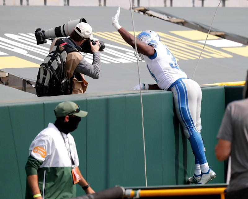 Detroit Lions running back Kerryon Johnson (33) celebrates a touchdown by jumping into the stands with no fans during the first quarter of the Green Bay Packers play the Detroit Lions at Lambeau Field in Green Bay on Sunday, Sept. 20, 2020.