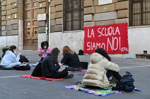 19 November 2020, Italy, Rom: Schoolgirls are sitting in front of their high school, on which a banner with the inscription La Scuola siamo Noi (We are the school) is hanging. They protest against having to teach online and demand a return to face-to-face teaching. The government had introduced so-called homeschooling as a measure in the wake of the Corona pandemic to protect against further infection. Photo: Johannes Neudecker/dpa (Photo by Johannes Neudecker/picture alliance via Getty Images) (Photo: picture alliance via Getty Images)