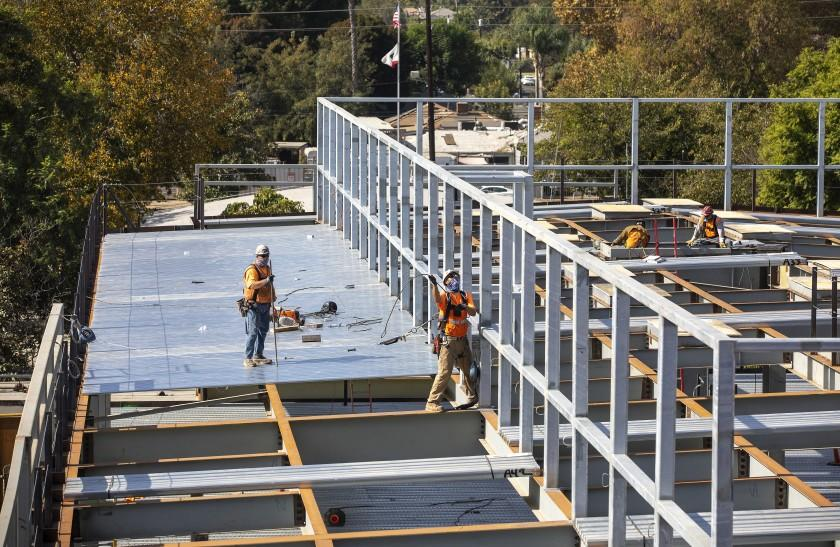 RESEDA, CA - NOVEMBER 02, 2020: Iron workers Greg Wright, left, and Robert Hernandez work on installing metal decking on a building under construction at Cleveland Charter High School in Reseda that will have general classrooms. Cleveland Charter High School is undergoing a comprehensive modernization project. (Mel Melcon / Los Angeles Times)