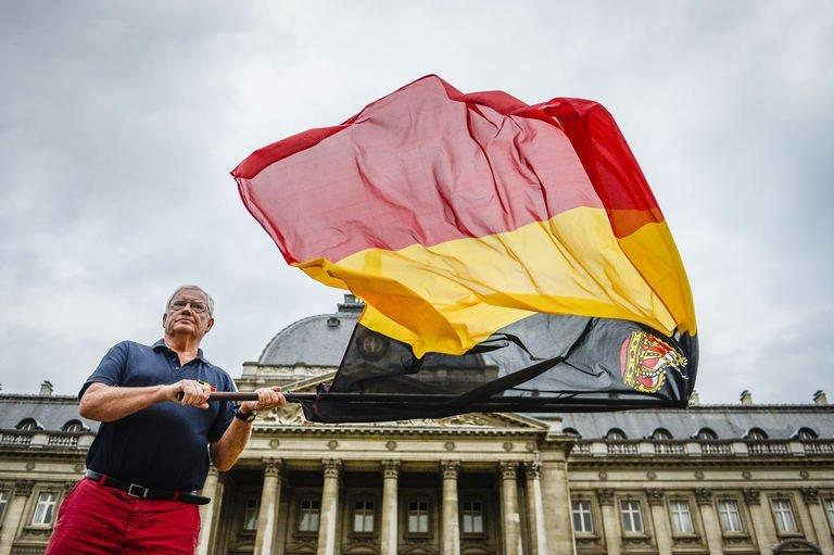 A waves a Belgian flag in front of the royal palace at the Paleizenplein - Place des Palais in Brussels, on July 3, 2013. King Albert II of Belgium announced to the Belgian people his abdiction from the throne on July 21