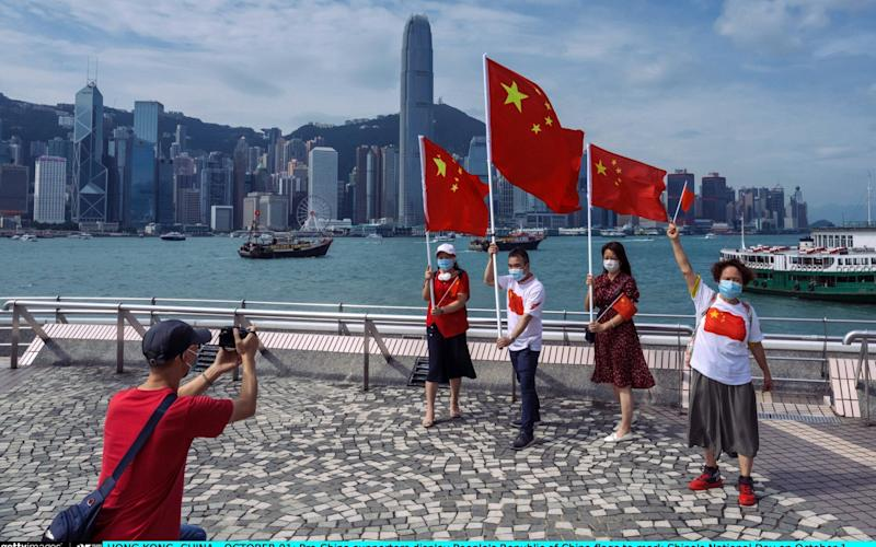Pro-China supporters display People's Republic of China flags to mark China's National Day in Hong Kong - Billy H.C. Kwok /Getty Images AsiaPac