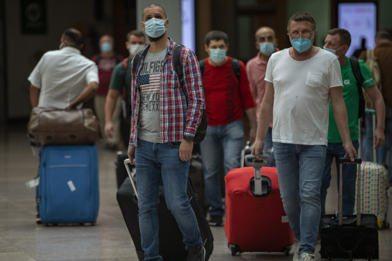 Passengers arrive at the Barcelona airport in Barcelona, Spain, Tuesday, June 30, 2020. The European Union on Tuesday is announcing a list of nations whose citizens will be allowed to enter 31 European countries. As Europe's economies reel from the impact of the coronavirus, southern EU countries like Greece, Italy and Spain are desperate to entice back sun-loving visitors and breathe life into their damaged tourism industries. (AP Photo/Emilio Morenatti)