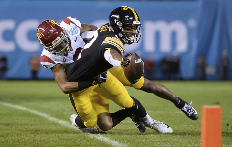 Iowa wide receiver Brandon Smith, right, reaches forward as he goes out of bounds as he is tackled by Southern California cornerback Olaijah Griffin during the first half of the Holiday Bowl NCAA college football game Friday, Dec. 27, 2019, in San Diego. (AP Photo/Orlando Ramirez)