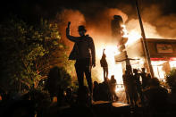 Protesters gather in front of a burning fast food restaurant, May 29, 2020, in Minneapolis. Protests over the death of George Floyd, a black man who died in police custody, broke out in Minneapolis for a third straight night. The image was part of a series of photographs by The Associated Press that won the 2021 Pulitzer Prize for breaking news photography. (AP Photo/John Minchillo)
