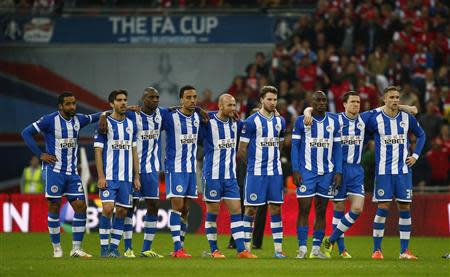 Wigan Athletic's players react during their penalty shoot-out against Arsenal during their English FA Cup semi-final soccer match at Wembley Stadium in London April 12, 2014. REUTERS/Eddie Keogh