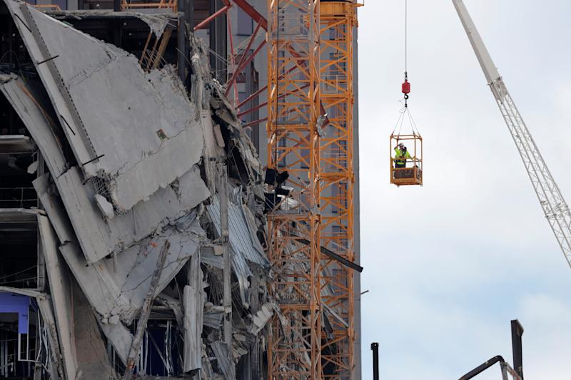 Workers are raised in a crane bucket to prepare two unstable cranes for implosion at the collapse site of the Hard Rock Hotel, which underwent a partial, major collapse while under construction last Sat., Oct., 12, in New Orleans, Saturday, Oct. 19, 2019. (AP Photo/Gerald Herbert)