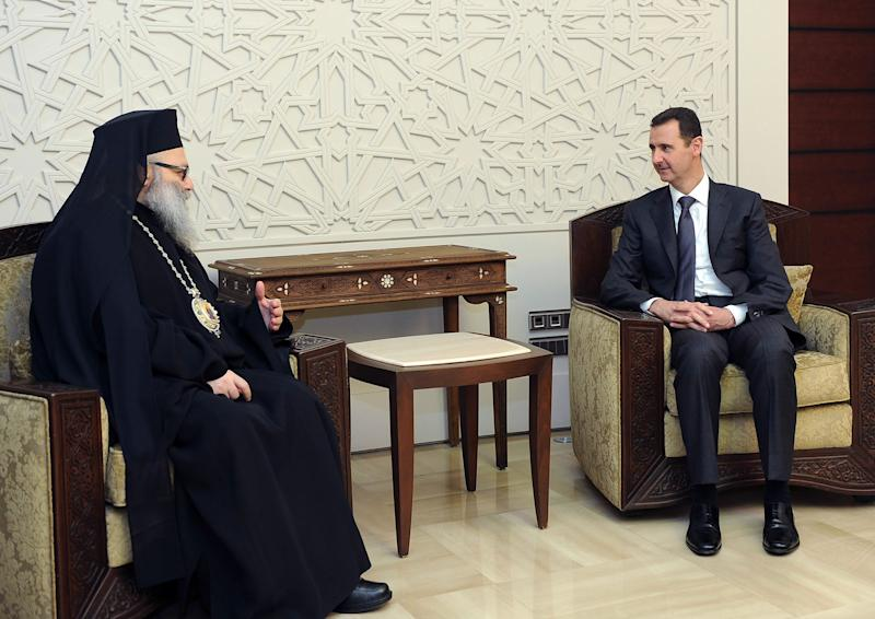In this photo released by the Syrian official news agency SANA, Syrian President Bashar Assad, right, meets with Patriarch John Yazigi, the Eastern Orthodox Patriarch of Antioch and All the East, in Damascus, Syria, Monday, Feb. 11, 2013. Syrian rebels captured the country's largest dam on Monday after days of intense clashes, giving them control over water and electricity supplies for much of the country in a major blow to President Bashar Assad's regime. (AP Photo/SANA)