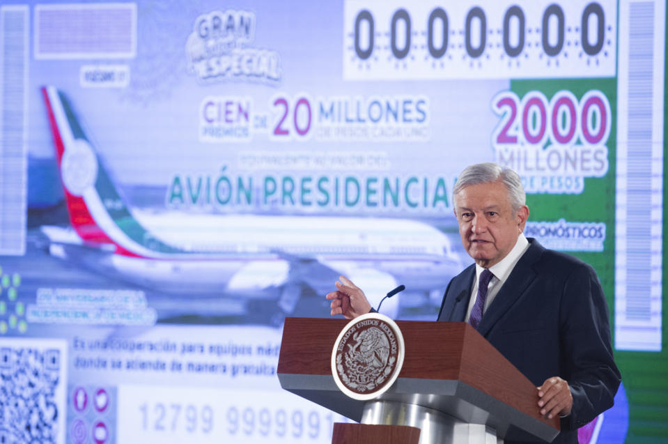 """In this photo provided by Mexico's Presidential Press Office, President Andres Manuel Lopez Obrador stands in front of an image of a raffle ticket featuring the presidential plane, in his morning press conference at the National Palace in Mexico City, Friday, Feb. 7, 2020. Lopez Obrador announced that the raffle of the Boeing Dreamliner will be symbolic, awarding total prize money of $100 million, which lottery tickets state is """"equivalent to the value of the presidential jet."""" (Mexico's Presidential Press Office via AP)"""