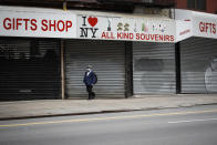 """FILE - In this April 27, 2020, file photo, a pedestrian wearing a protective mask walks along shuttered storefronts on Canal Street during the coronavirus outbreak in New York. As some governors across the United States begin to ease restrictions imposed to stop the spread of the coronavirus, hopes are soaring that life as we knew it might be returning. But the plans emerging in many states indicate that """"normal"""" is still a long way off. (AP Photo/John Minchillo)"""