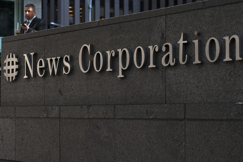 A passer-by stands in front of the News Corporation building in New York