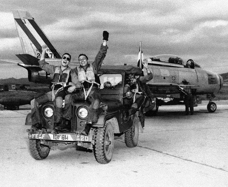 FILE - This July 29, 1953 black-and-white file photo shows happy fliers of the 18th Fighter Bomber wing let the world know how they feels as the come back from one of the combat missions over North Korea to learn of the armistice signing. From left are: 2nd Lt. John Putty, Dallas, Tex.; 1st Lt. James A. Boucek, Ottawa, Kan.: and 1st Lt. Richard D. Westcott, Houston, Tex., waving from back seat of jeep. Sixty years after it finished fighting in Korea, the U.S. is still struggling with two legacies that are reminders of the costs -- political, military and human -- that war can impose on the generations that follow. The first is the leading role that America still is committed to playing in defending South Korea should the 1950-53 Korean War re-ignite. (AP Photo, File)