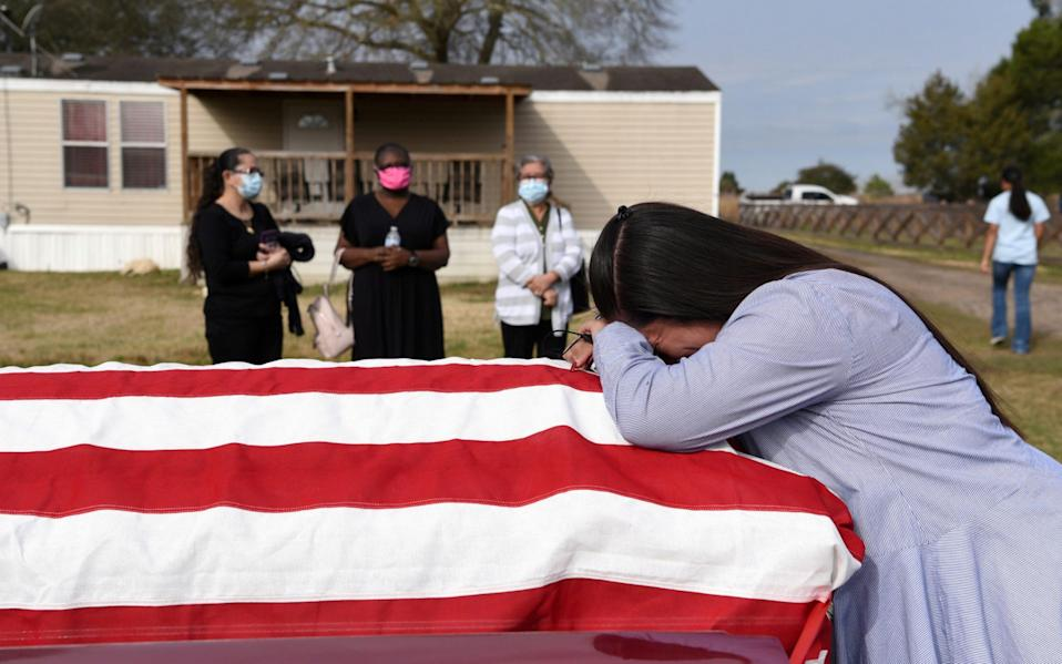 Lila Blanks holds the casket of her husband, Gregory Blanks, 50, who died of the Covid, ahead of his funeral in San Felipe, Texas - Callaghan O'Hare/Reuters