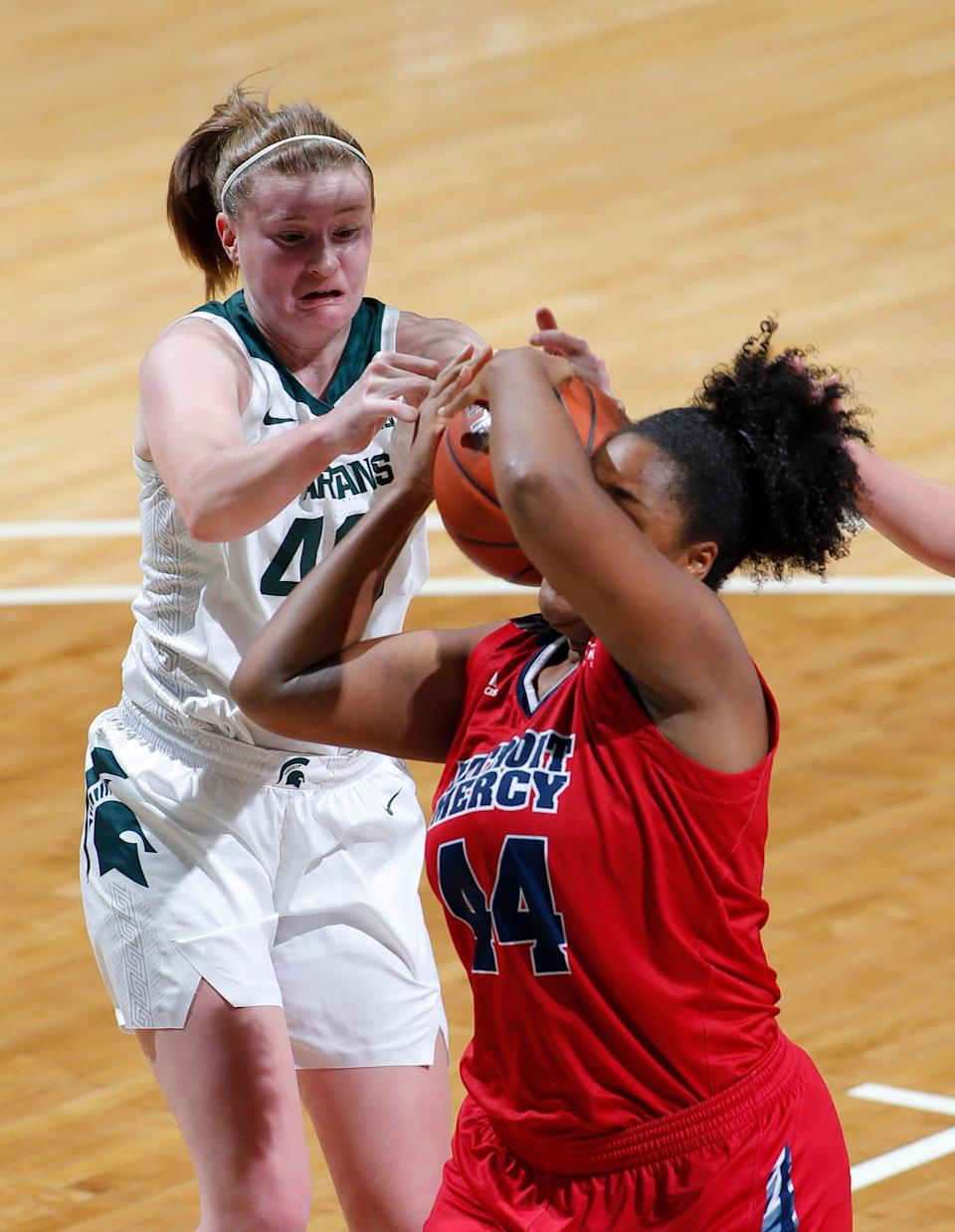 Michigan State's Julia Ayrault, left, and Detroit's Maxine Moore battle for a rebound, Wednesday, Dec. 2, 2020, in East Lansing, Mich. Michigan State won 82-45.
