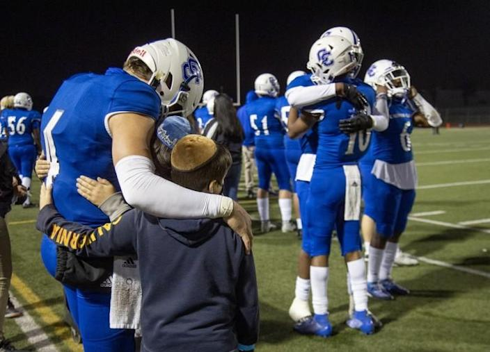 Culver City quarterback Zevi Eckhaus consoles his brothers Yanki and Chaim after his final high school game.