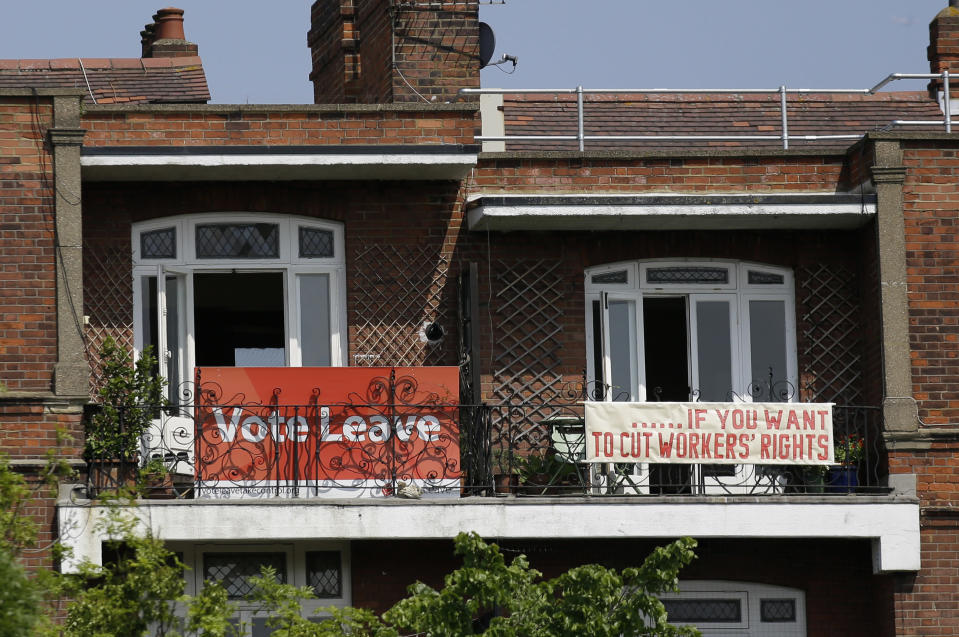 FILE - In this Friday, May 27, 2016 file photo, banners of opposing views on the Brexit referendum are displayed on the balconies of two neighbouring flats in the Gospel Oak area of north London. Eleven months after Britain's formal departure from the EU, Brexit becomes a fact of daily life on Friday, Jan. 1, 2021. Brexit marks the end of an awkward relationship. Britain joined the then-European Economic Community in 1973, but never fully embraced the bloc's project of ever-closer integration. (AP Photo/Matt Dunham, file)