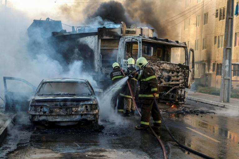 Brazilian firefighters put out a burning truck and car during a wave of gang violence in the northeast in January: far-right President Jair Bolsonaro has succeeded in loosening gun ownerership laws in what he says is a move to tackle rampant violence