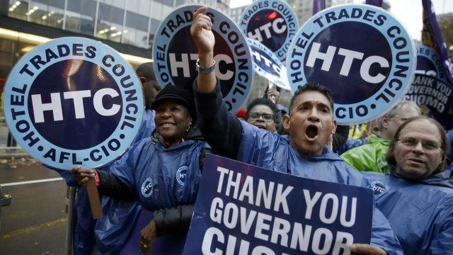 Participants cheer at a home care and healthcare workers rally in support of a $15 minimum wage, Tuesday, Nov. 10, 2015, in New York. New York Gov. Andrew Cuomo is raising the minimum wage for about 10,000 state workers to $15 an hour over the next six years.