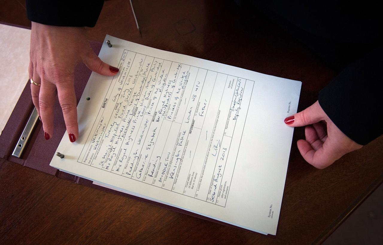 Westminster City Council registrar Alison Cathcart holds a copy of the birth register for Prince George of Cambridge which was signed by his father, the Duke of Cambridge at Kensington Palace this morning.