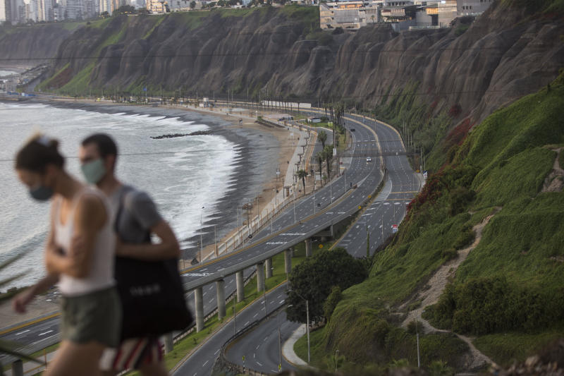 With an empty highway in the background, Liza Mell, 26, and Jean-Marie Landre, 27, both French citizens living in Lima, Peru, walk wearing a protective mask as a precaution against the spread of the new coronavirus, Saturday, March 21, 2020. (AP Photo/Rodrigo Abd)