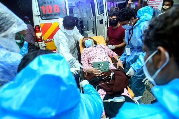 Health workers transfer an inured passenger on a stretcher to take her inside a hospital in Kozhikode, Kerela, after an Air India Express jet crashed by overshooting the runway at Calicut International Airport.