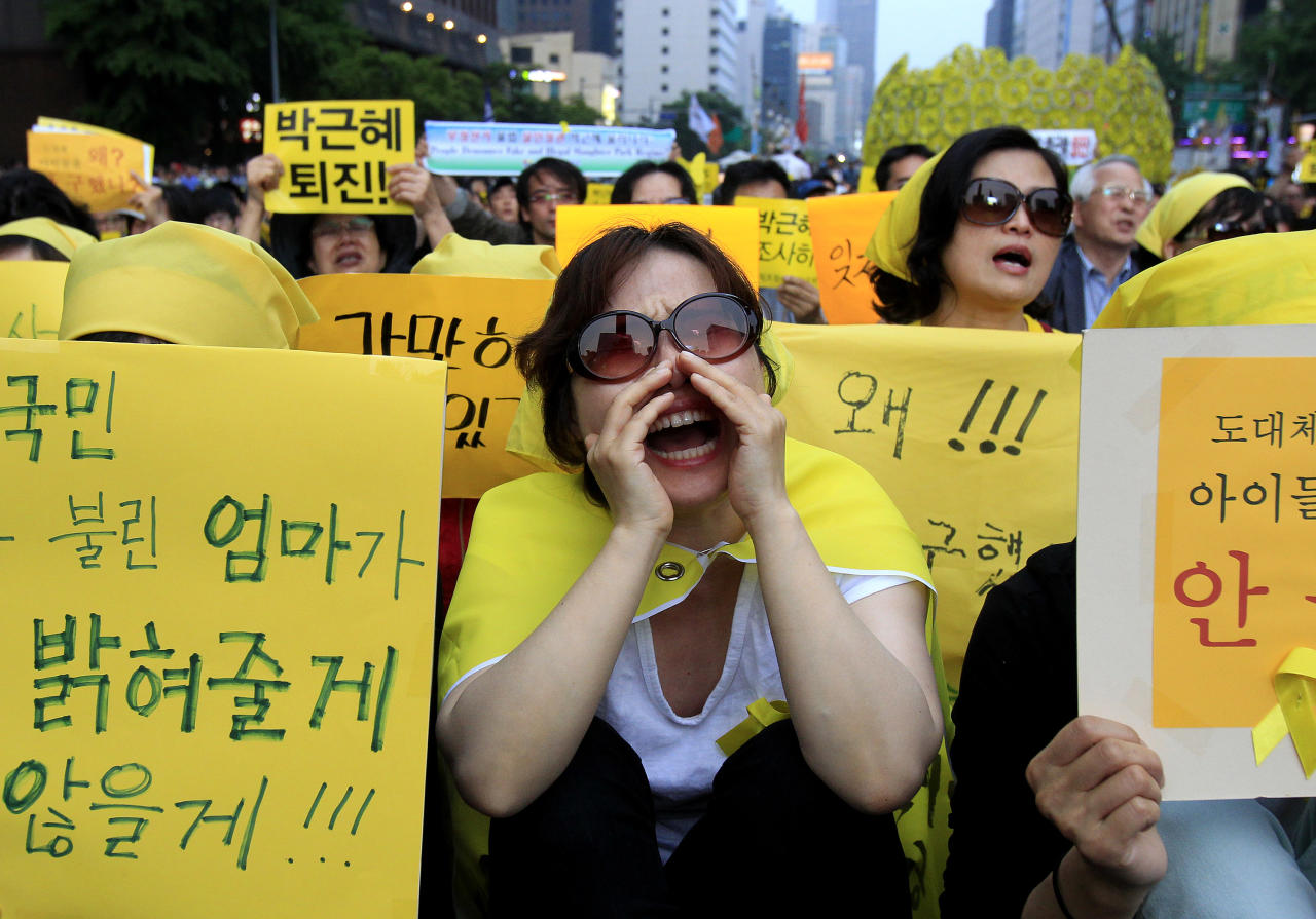 "A woman shouts names of victims during a rally to demand the government to seek the truth in poor handling of the sinking of the ferry Sewol, in Seoul, South Korea, Saturday, May 24, 2014. More than 300 people are dead or missing in the water off the southern coast in the disaster that caused widespread grief, anger and shame. The letters at cards read "" President Park Geun-hye should assume the responsibility and Out, President Park Geun-hye"". (AP Photo/Ahn Young-joon)"