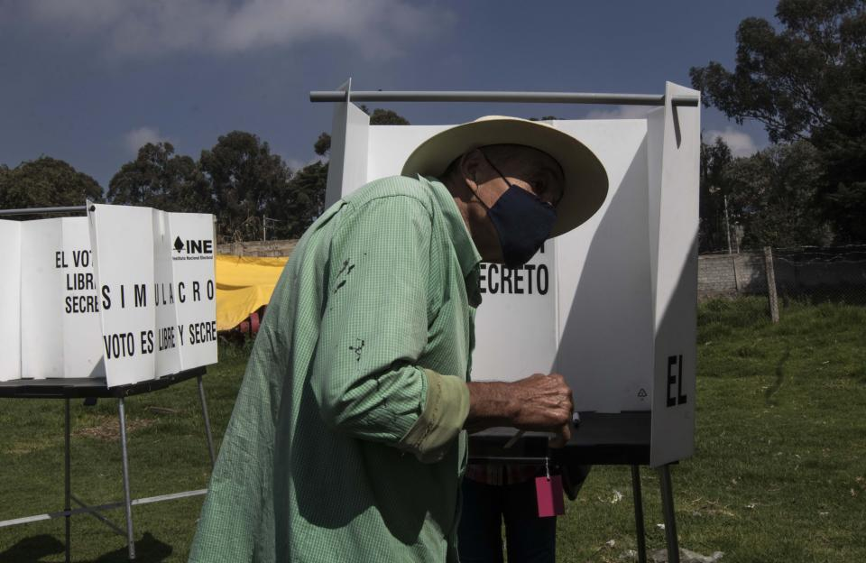 A man casts his vote in a non-binding referendum on whether Mexican ex-presidents should be tried for any illegal acts during their time in office, in San Miguel Topilejo, Mexico City, Sunday, August 1, 2021. (AP Photo/Christian Palma)