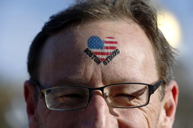 """Rob Ordman, of Calgary Alberta, wears the slogan """"Boston Strong"""" on his head near the finish line before the start of 118th Boston Marathon Monday, April 21, 2014 in Boston. He's supporting his wife Beth, who is running in the race. (AP Photo/Charles Krupa)"""