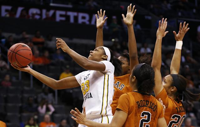 West Virginia guard Bria Holmes (23) shoots in front of Texas forward Nneka Enemkpali, guard Brianna Taylor (20) and guard Celina Rodrigo (2) in the second half of an NCAA college basketball game in the semifinals of the Big 12 Conference women's tournament in Oklahoma City, Sunday, March 9, 2014. West Virginia won 67-60. (AP Photo/Sue Ogrocki)