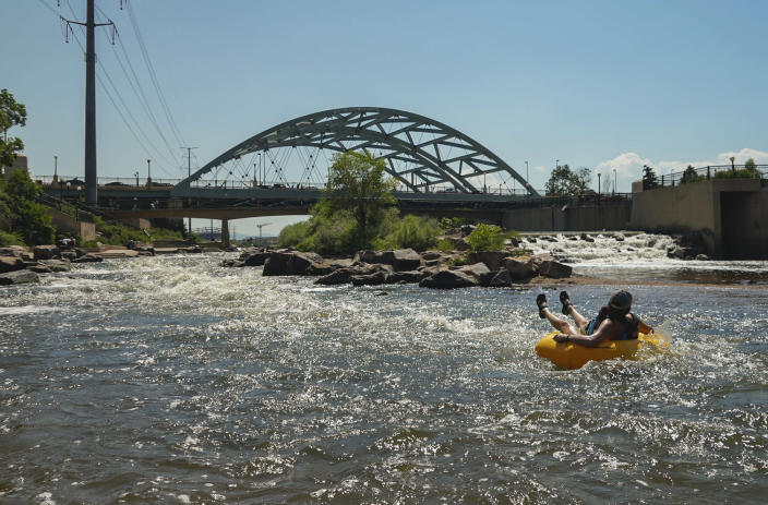 People cool off in the water at the confluence of the South Platte River and Cherry Creek in Denver, Monday, June 14, 2021. By mid-afternoon, the temperature hit 96 degrees as part of the heat wave sweeping across the western U.S. (AP Photo/Brittany Peterson)