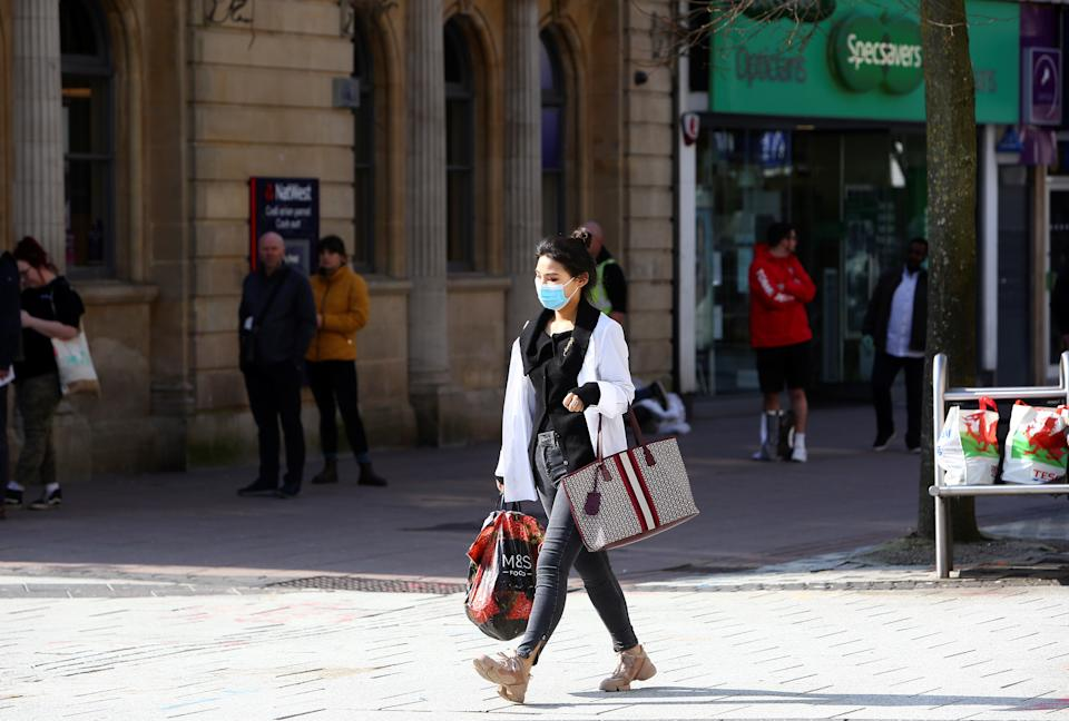 """A woman, wearing a face mask as a precautionary measure against covid-19, as people stand at a distance and queue to enter a bank in Cardiff, south Wales on the morning on March 24, 2020 after Britain's government ordered a lockdown to slow the spread of the novel coronavirus. - Britain was under lockdown March 24, its population joining around 1.7 billion people around the globe ordered to stay indoors to curb the """"accelerating"""" spread of the coronavirus. (Photo by GEOFF CADDICK / AFP) (Photo by GEOFF CADDICK/AFP via Getty Images)"""