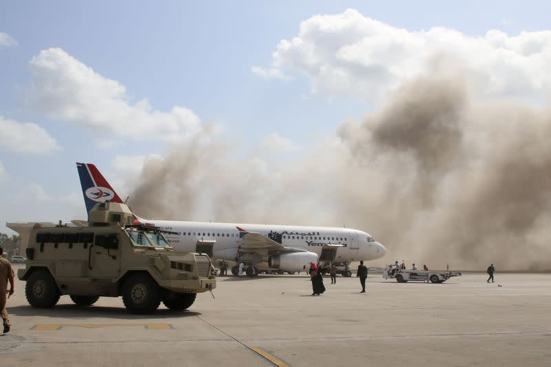 Military vehicle is seen on the tarmac as dust rises after explosions hit Aden airport, upon the arrival of the newly-formed Yemeni government in Aden