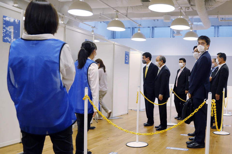Covid 19 Vaccine Minister Taro Kono, center left, and Masayoshi Son, chief executive of technology company SoftBank Group Corp., center right, visit an inoculation site set up by Japanese technology company SoftBank Group Corp. at a WeWork office Tuesday, June 15, 2021, in Tokyo. Japanese companies have joined the effort to speed up the country's lagging coronavirus vaccine rollout before the Tokyo Olympics begin next month. (AP Photo/Yuri Kageyama)