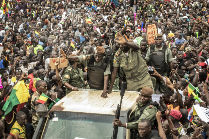 File-This Aug. 21, 2020, file photo shows an unidentified representative of the junta waves from a military vehicle as Malians supporting the recent overthrow of President Ibrahim Boubacar Keita gathers to celebrate in the capital Bamako, Mali. The U.N. humanitarian chief, Mark Lowcock, is hoping a major ministerial meeting on Tuesday, Oct. 20, 2020, will not only raise a billion dollars for the three countries at the epicenter of a humanitarian crisis in Africa's Sahel region -- Burkina Faso, Mali, and Niger -- but spur leaders to address the underlying drivers including increasing conflict and insecurity, weak governance, and a lack of development (AP Photo/File)