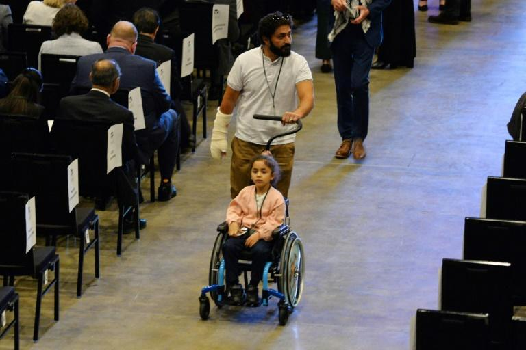Al Noor mosque shooting survivor Wasseim Alsati arrives with his daughter at the service. Fifty-one people were killed and dozens wounded in the attacks on two Christchurch mosques in 2019