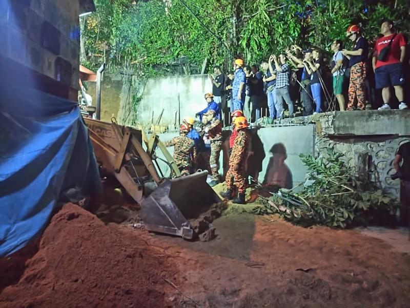 Fire and Rescue Department personnel search for victims of a landslide in Tanjung Bungah, George Town June 25, 2019. — Picture courtesy of the Penang police