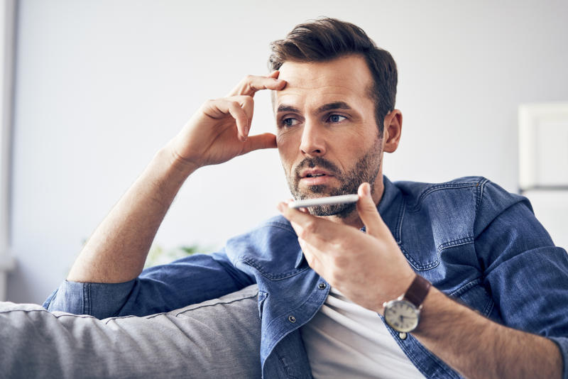 Man looks annoyed and stressed while talking on phone