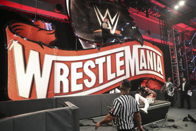 Kevin Owens jumps off a WrestleMania sign on Saturday night. (WWE)