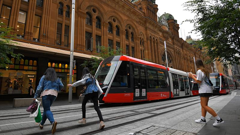 Pedestrians cross tram tracks in Sydney. An illegal crossing now attracts a fine of $76.