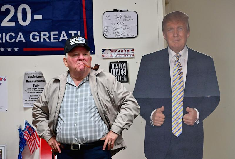 """President Donald Trump supporter Tom Kenney wearing a """"Cops for Trump"""" hat stands next to a cardboard cutout of the president as he watches the first presidential debate between Trump and Democratic presidential nominee and former Vice President Joe Biden on Tuesday in Old Forge, near Scranton, Pennsylvania."""