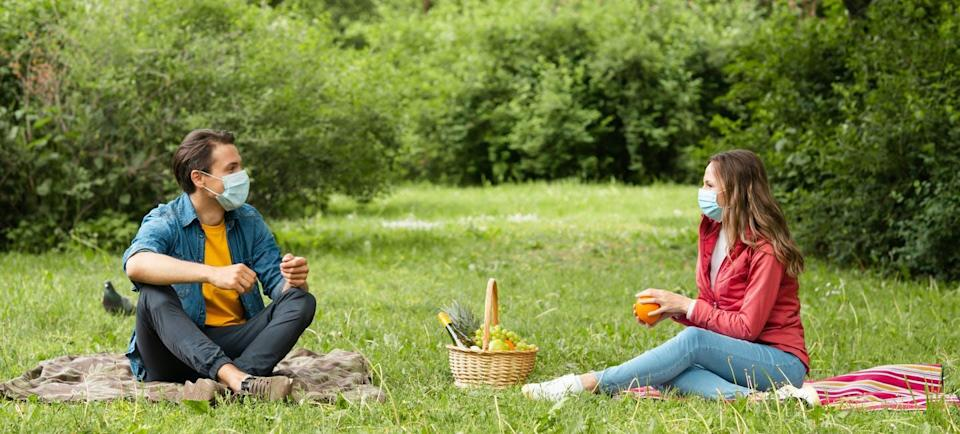 A couple with a picnic basket chatting with masks on at a social distance