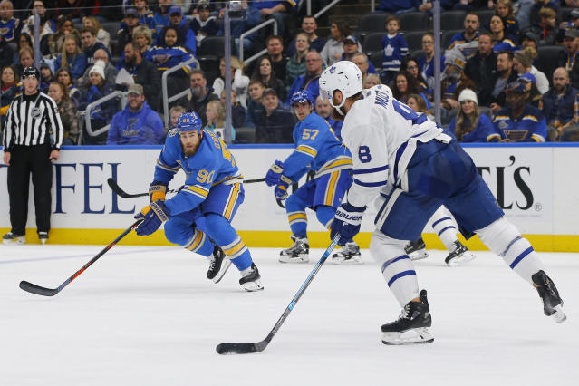 Toronto Maple Leafs' Jake Muzzin (8) looks to pass the puck as he is defended by St. Louis Blues' Ryan O'Reilly (90) during the second period of an NHL hockey game Saturday, Dec. 7, 2019, in St. Louis. (AP Photo/Billy Hurst)