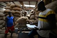 Workers weigh cocoa bags at the warehouse of the local farmers' collective in M'brimbo