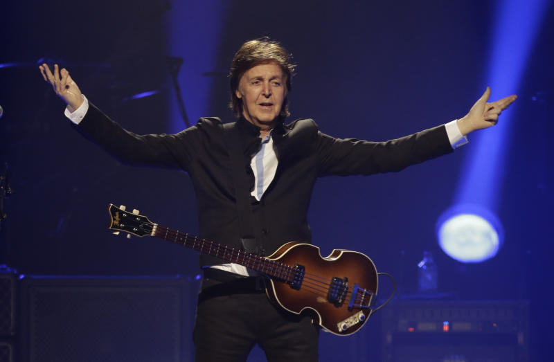 "FILE - In this Saturday, May 18, 2013 file photo, Paul McCartney performs during the first U.S concert of his ""Out There"" tour, in Orlando, Fla. McCartney made his first visit to the one-time home of the King of Rock 'N' Roll and left a gift behind. According to the official Twitter account of the former Beatle, McCartney dropped a personal guitar pick on Elvis Presley's grave, Sunday, May 26, 2013, and said it was ""so Elvis can play in heaven."" (AP Photo/John Raoux, File)"
