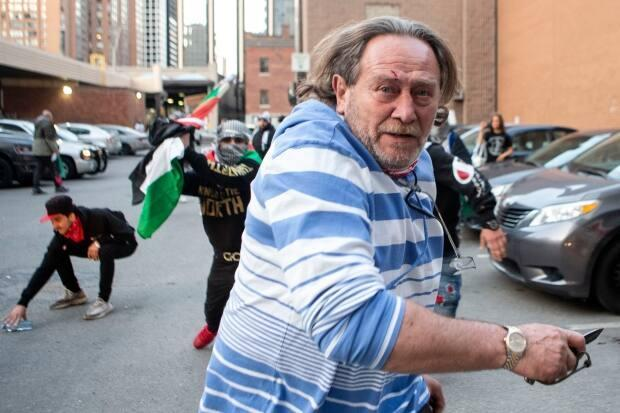 New images appear to show the man, believed to be the victim of an assault by pro-Palestinians in Toronto on Saturday, was holding what looks like a knife during the altercation. (Chris Young/Canadian Press - image credit)