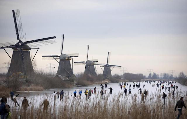 FILE - In this Jan. 3, 2009, file photo, people skate on frozen canals in Kinderdijk's Mill Area, near Rotterdam, Netherlands. There is nothing more mythical in Dutch sports than an age-old 11-city race skating across lakes and canals in bone-numbing cold from dawn to dusk. No wonder the Netherlands is the greatest speedskating nation in the world. And with Sven Kramer and Ireen Wust leading the way on big oval in Sochi they are bent on proving it again. (AP Photo/Peter Dejong, File)