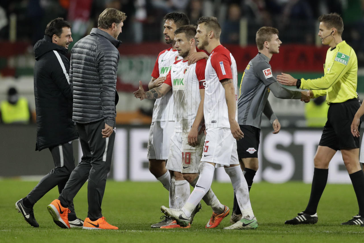 Leipzig head coach Ralph Hasenhuettl argues to Augsburg's Daniel Baier, center, after the German Soccer Bundesliga match between FC Augsburg and RB Leipzig in Augsburg, Germany, Tuesday, Sept. 19, 2017. (AP Photo/Matthias Schrader)