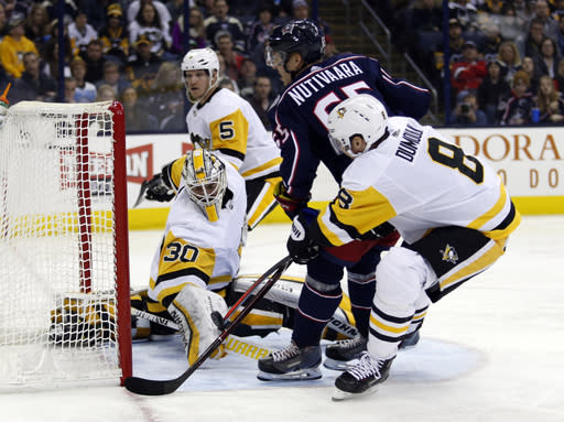 Pittsburgh Penguins goalie Matt Murray (30) makes a stop against Columbus Blue Jackets defenseman Markus Nutivaara (65), of Finland, as Penguins defensemen Zach Trotman (5) and Brian Dumoulin (8) defend during the second period of an NHL hockey game in Columbus, Ohio, Saturday, March 9, 2019. (AP Photo/Paul Vernon)